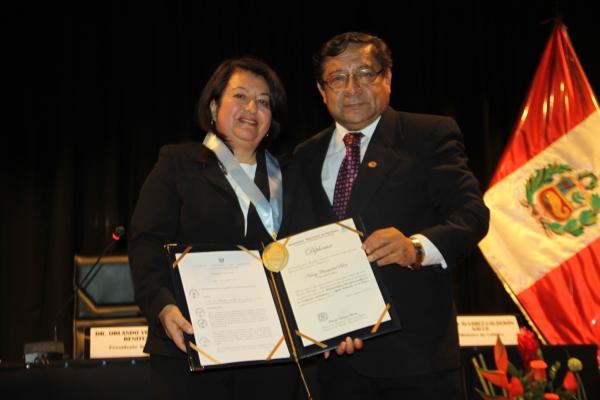 Nancy Chasquibol recibiendo reconocimiento del presidente de la ANR, Orlando Velásquez Benites.